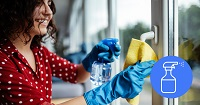Woman wearing disposable gloves using a spray bottle and cloth cleaning door handle on glass door.