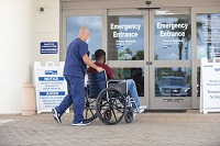 Patient in wheelchair being pushed by associate to the Emergency Entrance doors at Holmes Regional Medical Center.