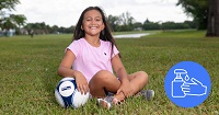 Girl wearing pink shirt sitting on grass smiling holding a soccer ball .