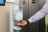 Hand under automatic floor standing hand sanitizer dispenser next to elevator door.