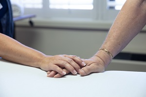 Hands holding on a hospital bed