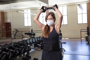 Woman(Jan) lifting weight with facemask on in the Pro-Health & Fitness gym.