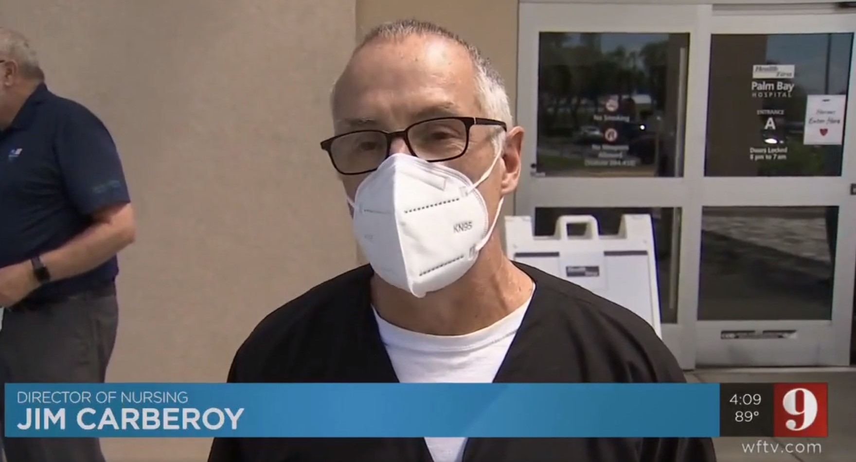 Director of Nursing, Jim Carberoy wearing mask in front of Health First's Palm Bay Hospital Entrance A.