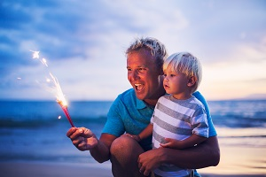Man kneeling with a boy at beach and man is holding a sparkler.