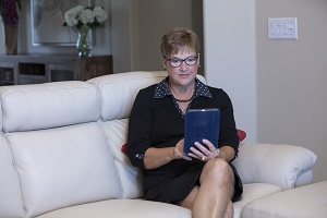 Woman sitting on couch with iPad during Virtual Visit