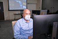 Wayne Struble Wearing Mask sitting at a computer.