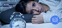 Woman laying in bed at nightime with eyes open looking at desktop standing clock.