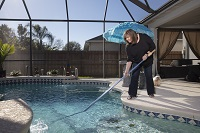Woman Vacuuming Pool.